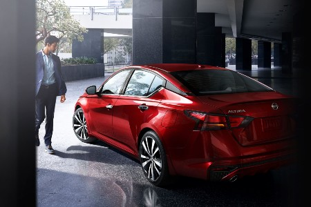 Rear driver angle of a red 2020 Nissan Altima with a man walking towards it