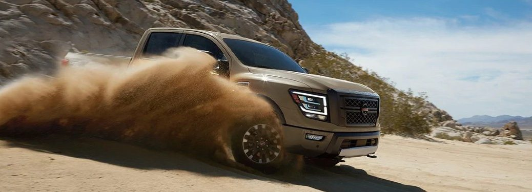 Front passenger angle of a tan 2020 Nissan TITAN driving through sand