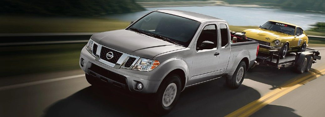 Front driver angle of a silver 2021 Nissan Frontier towing another car