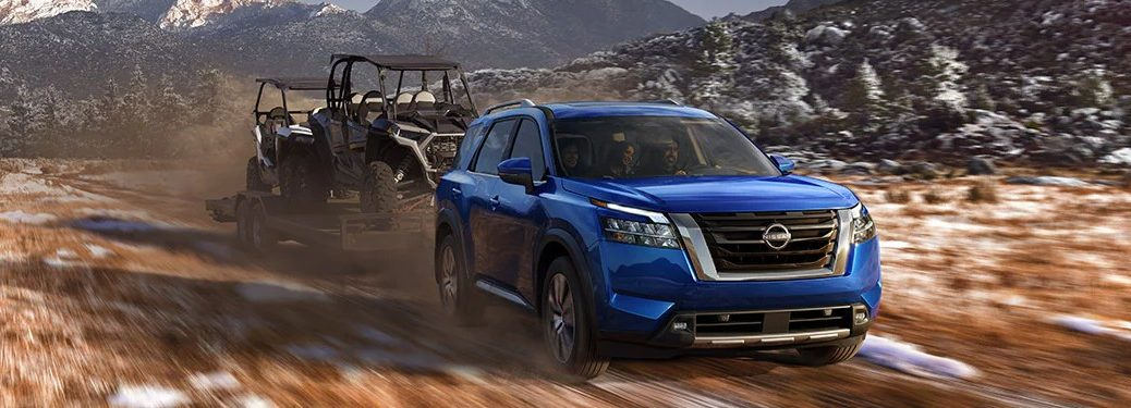 Front passenger angle of a blue 2022 Nissan Pathfinder towing 4-wheelers