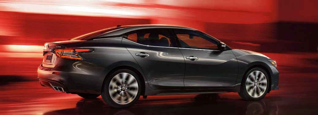 Rear passenger angle of a black 2020 Nissan Maxima driving with a blurry red background behind it