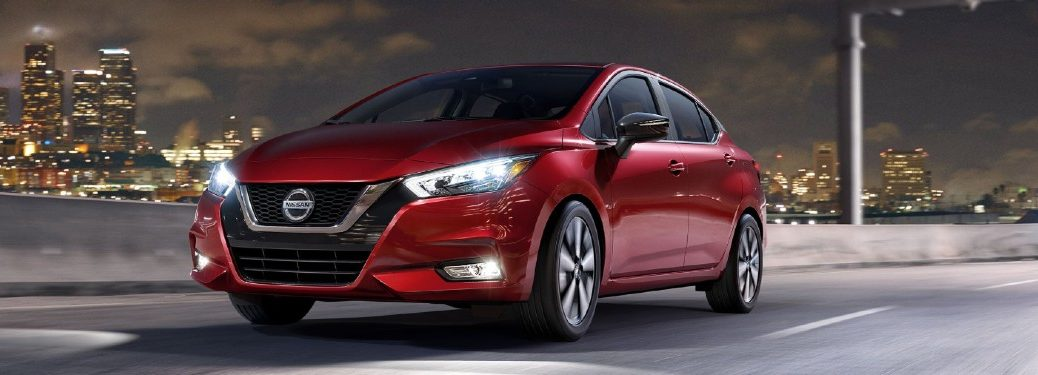 Front driver angle of a red 2020 Nissan Versa with a city in the background