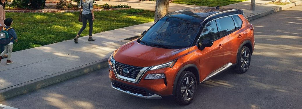 Front driver angle of an orange 2021 Nissan Rogue driving in a city