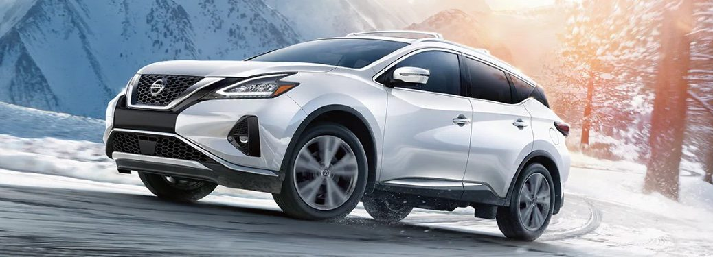Front driver angle of a white 2021 Nissan Murano driving in winter