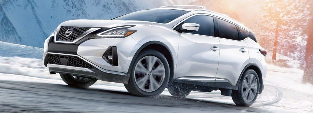 Front driver angle of a white 2019 Nissan Murano driving on a road during winter