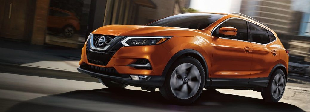 Front driver angle of an orange 2020 Nissan Rogue Sport driving in the city