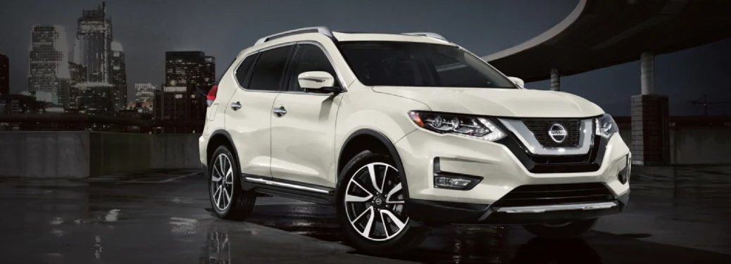 Front driver angle of a white 2020 Nissan Rogue on a dark background