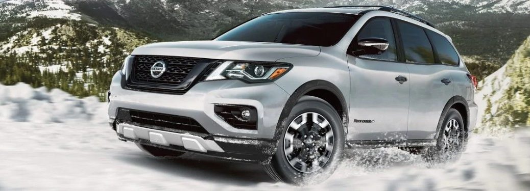 Front driver angle of a white 2020 Nissan Pathfinder Rock Creek Edition driving in snow