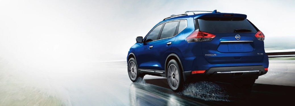Rear driver angle of a blue 2020 Nissan Rogue driving on a wet road