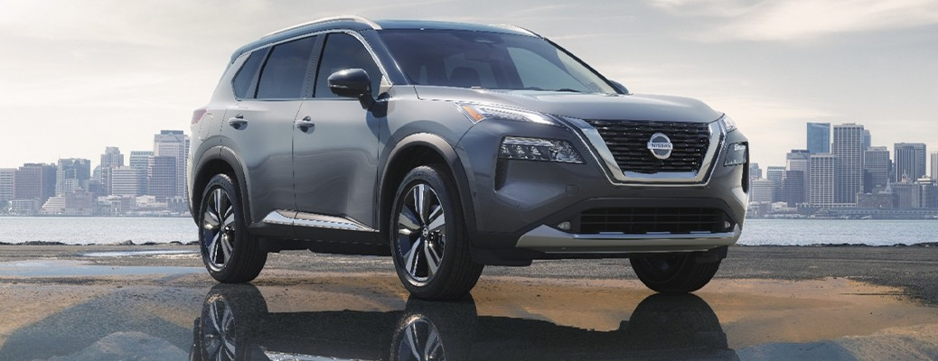 The 2021 Nissan Rogue parked on a puddle of water with a body of water and city landscape in the background