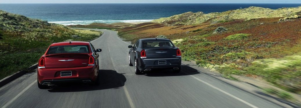 Red and black Chrysler 300 models driving down open road