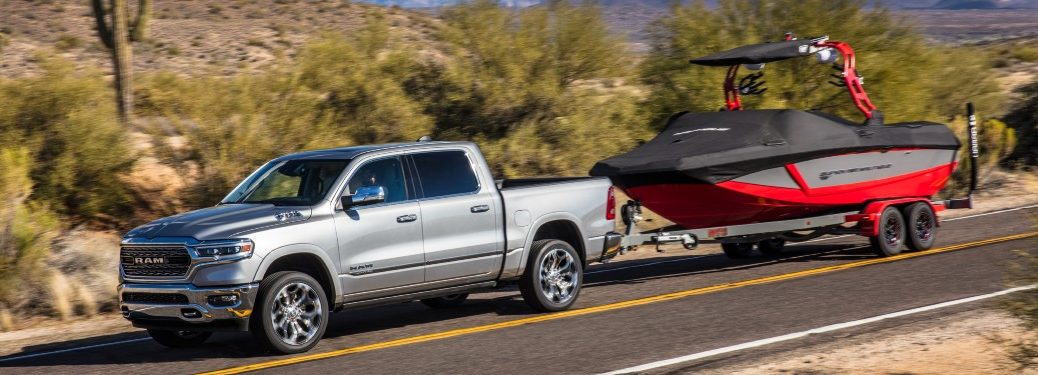 side view of a silver 2021 Ram 1500 towing a boat