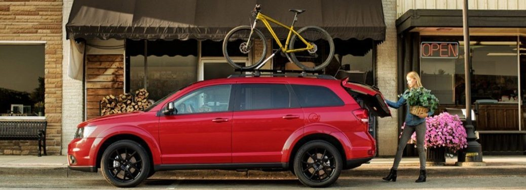 Driver angle of a red 2019 Dodge Journey parked on the side of the street with a yellow bike secured on its roof and a woman opening the back