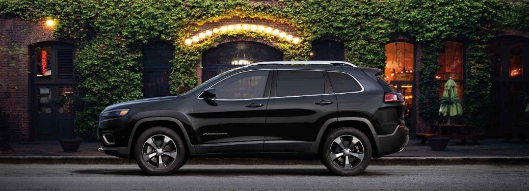 Driver angle of a black 2019 Jeep Cherokee parked in front of a building with plants covering the brick