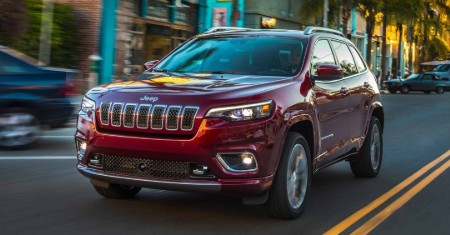 Front driver angle of a red 2019 Jeep Cherokee driving down a city road