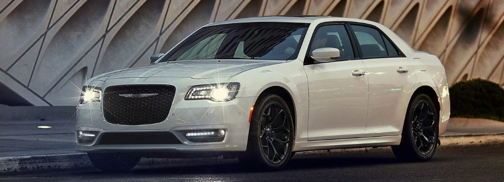 Front driver angle of a white 2019 Chrysler 300 with its headlights turned on