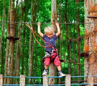 Little girl harnessed and completing a course in trees