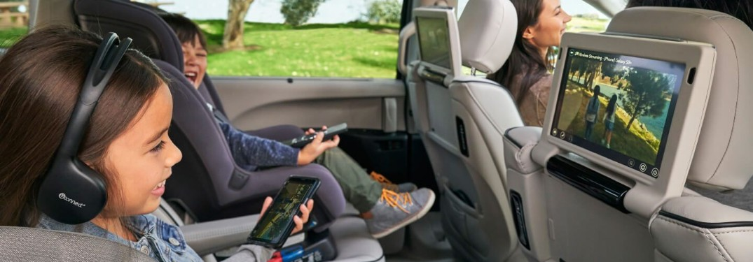 Girl smiling at the Uconnect screen while holding a phone and another child in a booster seat laughing in the 2019 Chrysler Pacifica