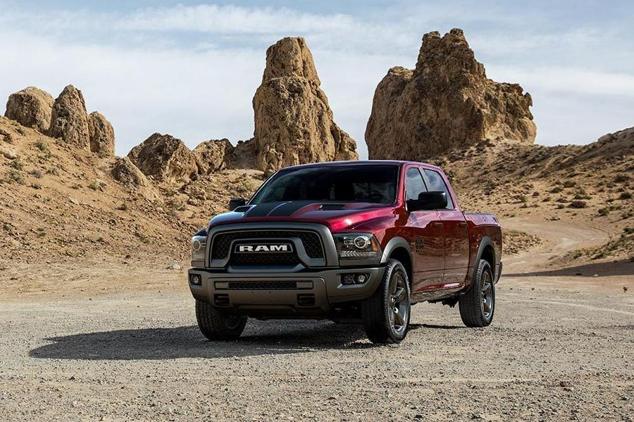 Front driver angle of a red 2019 Ram 1500 Classic parked outdoors with tall rocks in the background