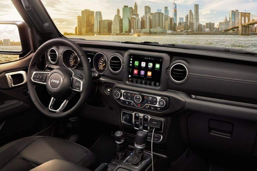Interior of 2020 Jeep Gladiator showing Apple CarPlay in front of city and water