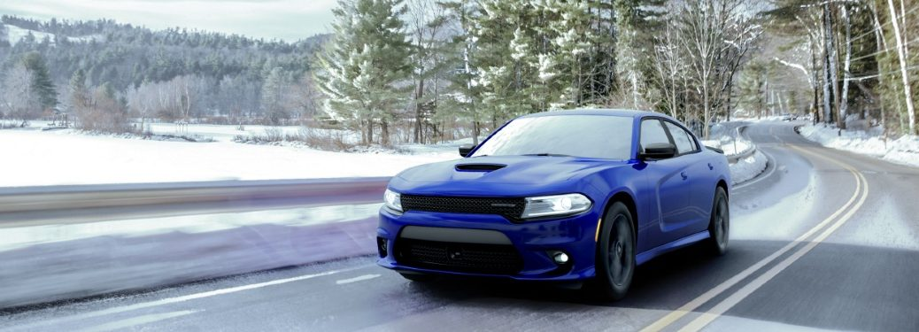 blue dodge charger driving by a frozen lake