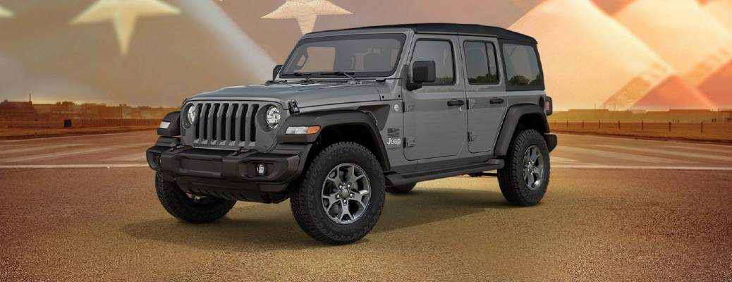 A granite-colored 2020 Jeep Wrangler Limited Edition Freedom model parked at an airforce base with an American flag faded into the background.