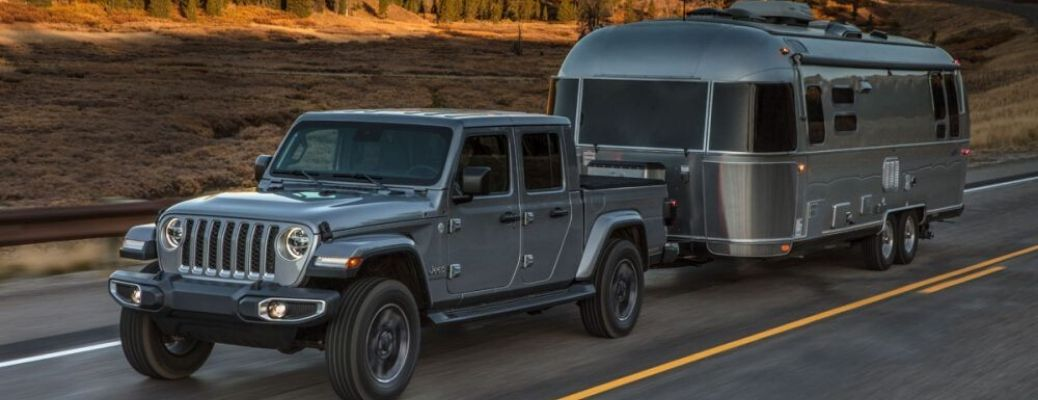 2020 Jeep Gladiator driving on the road and pulling a trailer