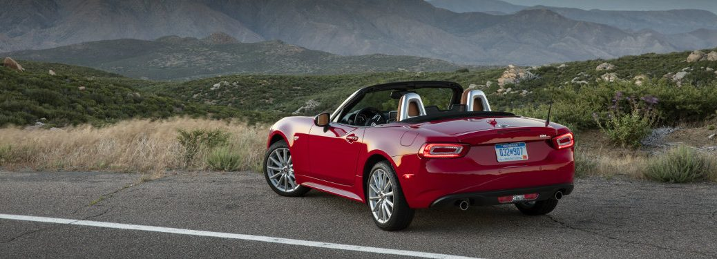red Fiat 124 Spider parked on side of road