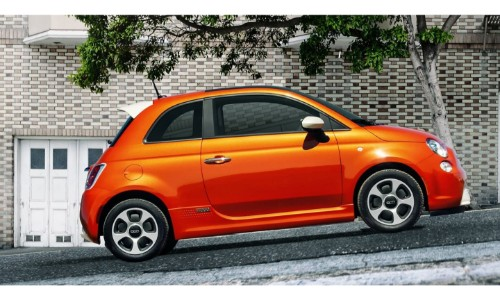 2018 Fiat 500e exterior side shot with orange paint job on an inclined suburban street