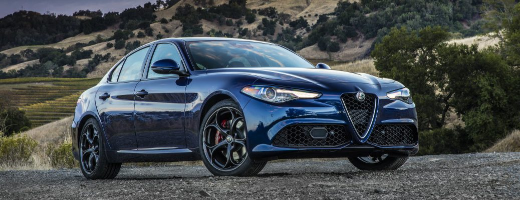 2019 Alfa Romeo Giulia exterior shot with blue color paint job parked on a gravel dirt road with forest hills and a setting sun sky in the background