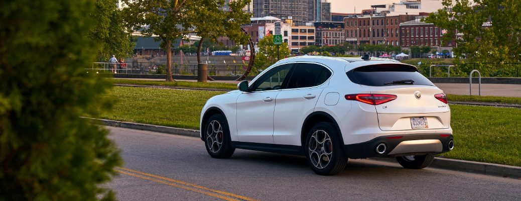 2019 Alfa Romeo Stelvio Ti Lusso exterior shot with tofeo white tri-coat paint color parked by the grass at a park outside of a city of skyscrapers