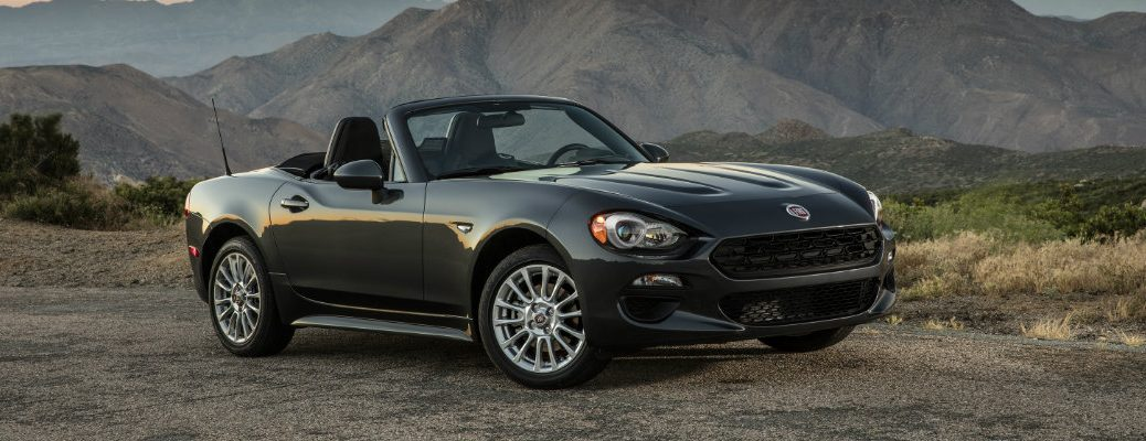 2019 Fiat 124 Spider Classica exterior shot with gray metallic paint color parked on a dirt road near roaming mountains