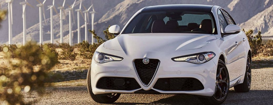 2019 Alfa Romeo Giulia exterior front shot with white paint color parked on gravel in an open field near bushes and a line of large wind turbine fans