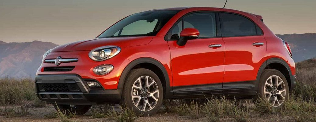 2019 Fiat 500X exterior side shot with red orange paint color parked in the wilderness among desert grass and mountains