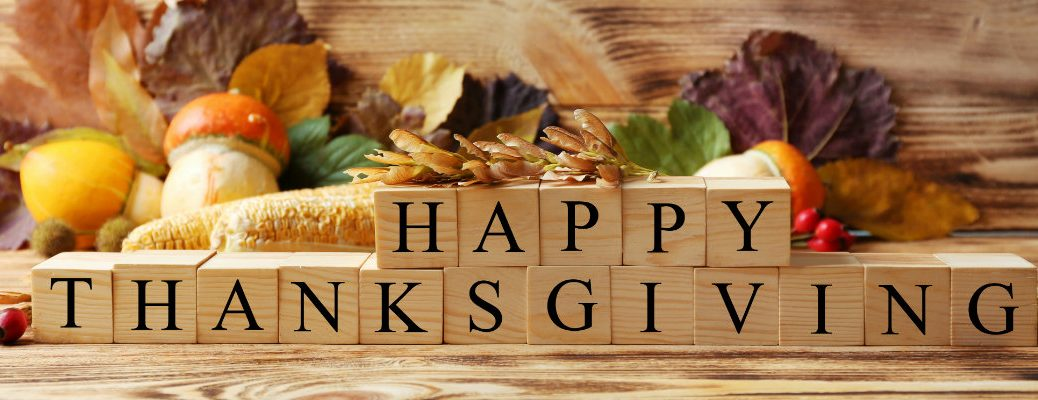 Happy Thanksgiving spelled out with building blocks with a cornucopia and other decorations behind it