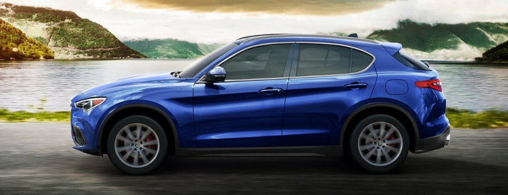 2019 Alfa Romeo Stelvio exterior side shot with blue paint color driving past a giant lake nestled between green mountains and clouds
