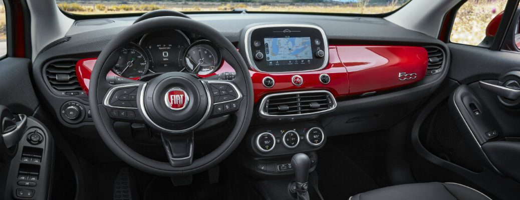 2019 Fiat 500X interior shot of front seating, dashboard layout and accents, infotainment display screen, and steering wheel with Fiat badge