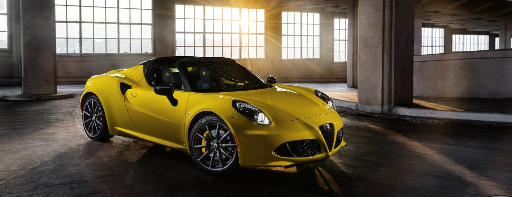 2019 Alfa Romeo 4C Spider exterior shot with yellow paint color parked inside a tower parking garage as the sun shines in
