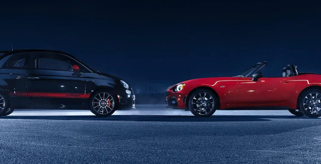 Fiat 124 Spider Abarth and Fiat 500 Abarth exterior side shot facing each other on a lit up asphalt plain at night flipped