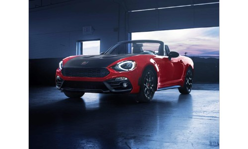 Fiat 124 Spider Abarth model exterior shot with red paint color parked just inside a garage as the door opens and lets the light of the sky in