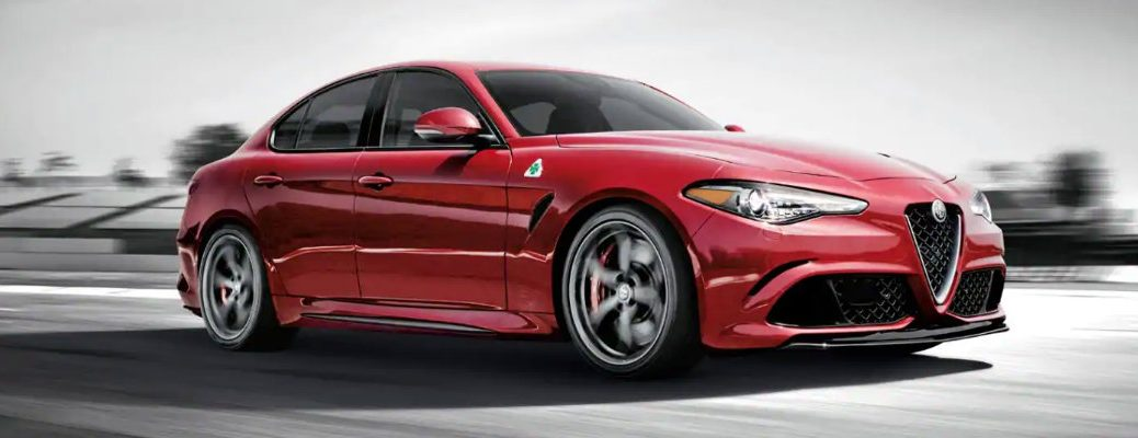 2019 Alfa Romeo Giulia Quadrifoglio Trim exterior side shot with red paint color driving along with a black and white background