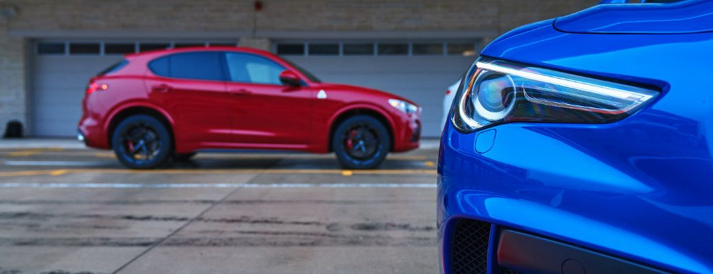 Alfa Romeo Stelvio Quadrifoglio SUVs with a closeup on a blue Stelvio headlight and a side profile shot of a red Stelvio in the background parked on an empty racing track