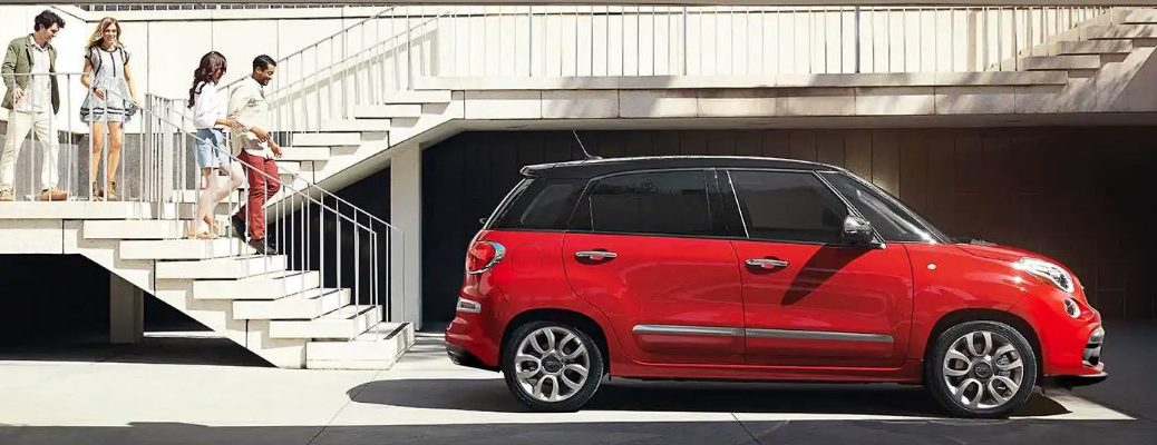 2019 Fiat 500L exterior side shot with red paint color parked at the bottom of a stairweel as a pair of couples descend towards it
