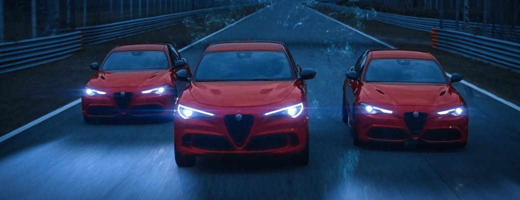 Alfa Romeo Experience soundtrack campaign still shot from new ode to joy commercial showing the Stelvio and Giulia models driving at night with LED headlights on