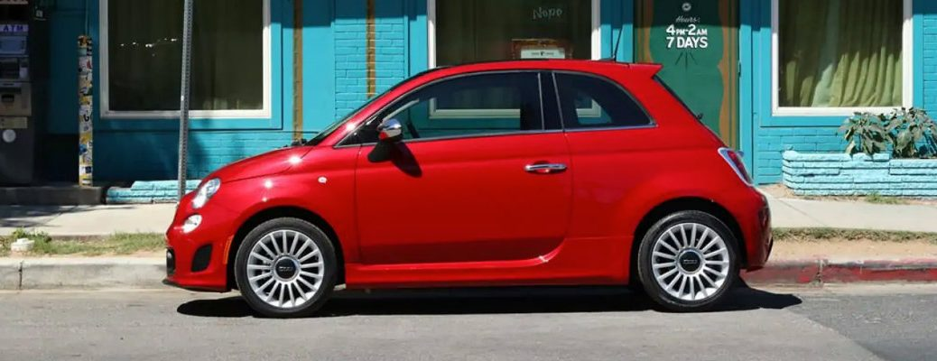 2019 Fiat 500 exterior side shot with red paint color parked by a tow sign next to a blue teal painted building