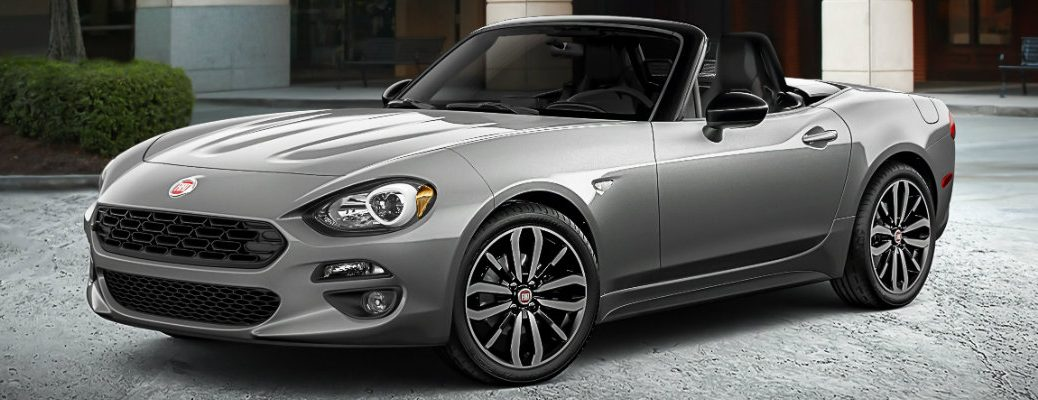 2019 Fiat 124 Spider Urbana Edition exterior shot with gray paint color parked outside a workshop mechanic garage