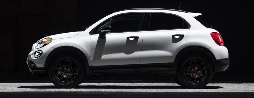 2019 Fiat 500X exterior side shot in a dark showroom with bianco gelato white clear-coat