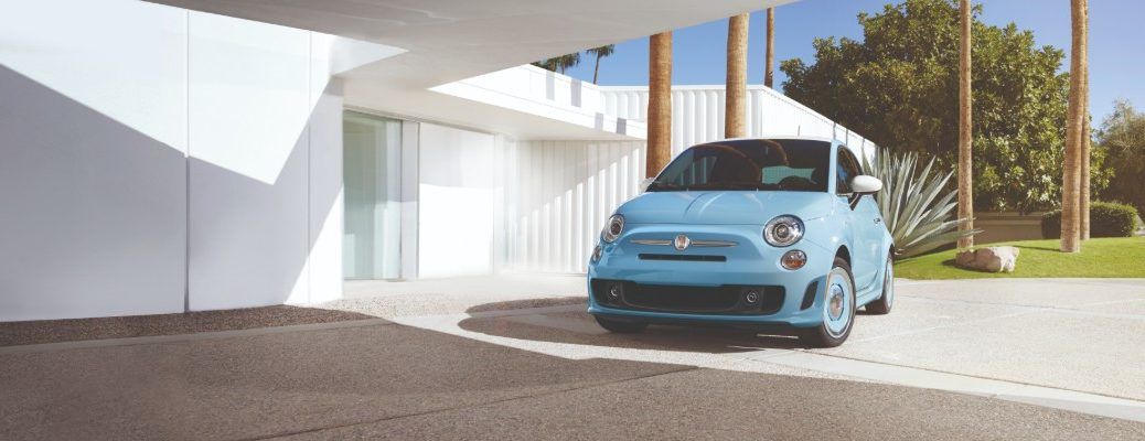 2019 Fiat 500 1957 Retro Edition exterior shot with Retro Light Blue paint color parked near a fancy white house near palm trees and brush