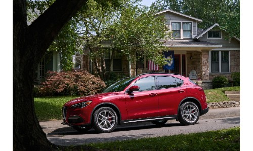 2019 Alfa Romeo Stelvio Ti Sport exterior side shot with red paint color parked under a tree next to a suburban house