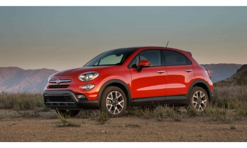 2019 Fiat 500X exterior shot with red paint job parked in an empty plain of wild grass and dirt with a mountain background